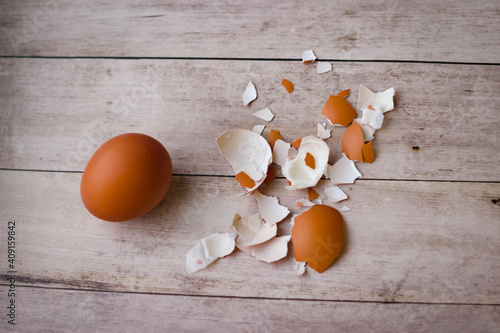 Fototapeta One whole chicken egg and the remains of a shell on a wooden background obraz