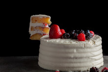 Close Up Image Of A Round Cake With Creamy White Icing And Assortment Of Berries Used As Decorative Toppings. Served On Dark Gray Black Granite Background. A Slice Is Elevated On The Side