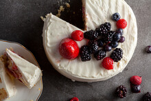 Close Up Image Of A Round Cake With Creamy White Icing And Assortment Of Berries Used As Decorative Toppings. Served On Dark Gray Black Background. Two Slices Are Removed And Placed On Porcelain Plate