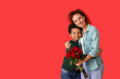 Leinwandbild Motiv African-American boy and his mother with flowers on color background