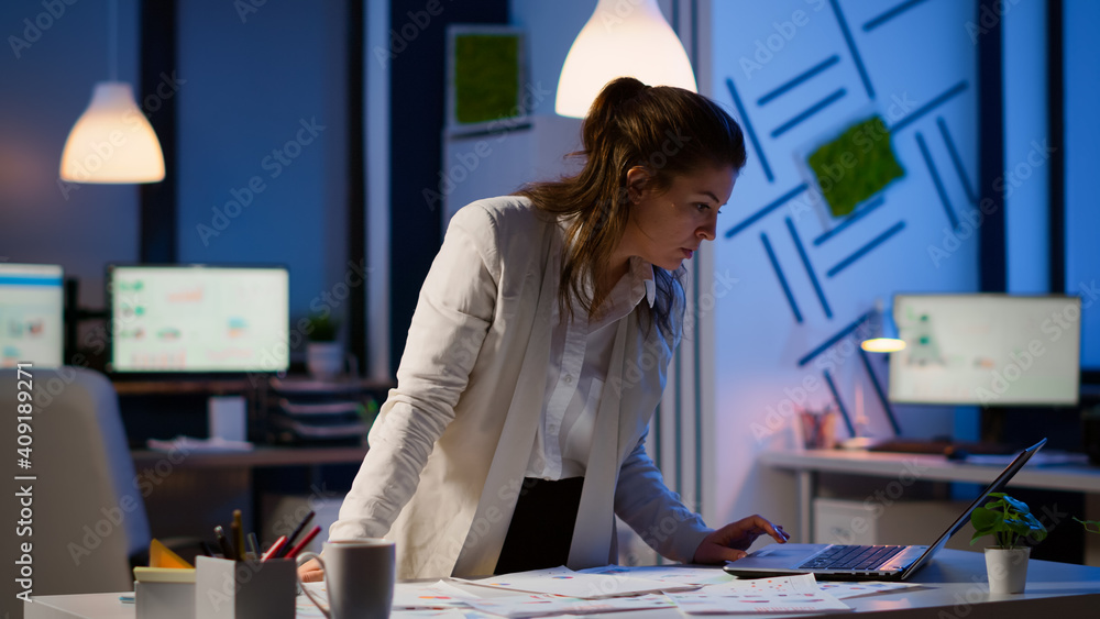 Fototapeta Happy business woman working on financial reports pointing to numbers, looking at laptop checking statistics graphs, having good results, smiling standing at desk late at night doing overtime.