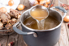 Saucepan With Bouillon With A Ladle On A Wooden Table. Bone Broth