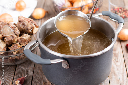 Fototapeta Saucepan with bouillon with a ladle on a wooden table. Bone broth obraz