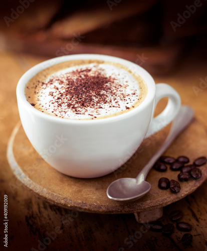 white cup with teaspoon on on wooden stand © Олена Сизоненко