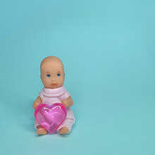 Vintage Bobblehead Holding A Heart On A Blue Background.