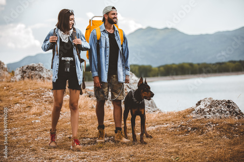 Leinwand Poster Hikers with backpacks and their doberman walking enjoying at the mountain lake