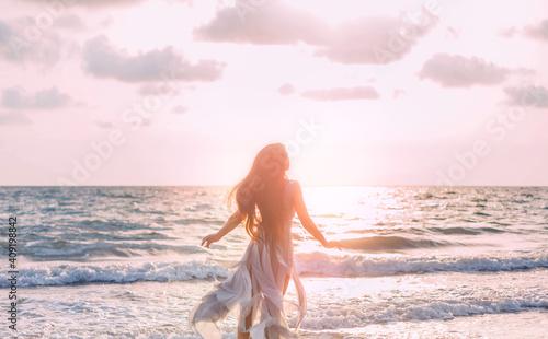 Fotografie, Tablou Silhouette of beautiful young happy woman tourist walks runs by coastline