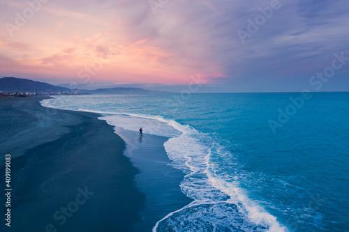 Carta da parati Uomo pesca da solo al tramonto in riva all'oceano