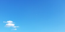 Blue Sky Background With A Small Group Of Tiny Clouds In The Left Lower Corner