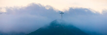 A Single Cross Stands On A Mountain Engulfed In White Clouds