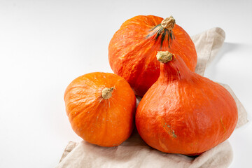 Hokkaido pumpkins. Hokkaido pumpkins on a light background. Pumpkins close-up. The concept of autumn harvest