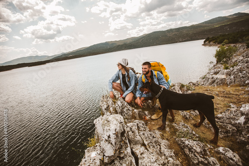 Foto Hikers with backpacks and their doberman  sitting on cliff enjoying at the mount