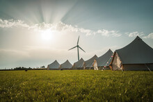 Wedding Teepee Tents With Flags In Field With Sunset And Wind Turbine Green Grass On Farmland No People Romantic Camping And Clamping Outdoors In The Evening Celebrations Electric Generator Sky