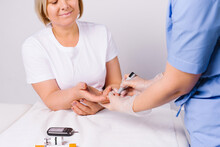 Hands Of A Healthcare Professional Using A Glucometer To Take An Analysis From An Older Woman On A White Background.