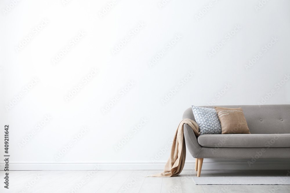 Fototapeta Grey sofa with pillows near white wall in stylish living room interior. Space for text