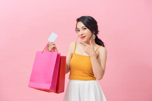 Portrait Of A Beautiful Girl Wearing Dress And Holding Colorful Shopping Bags And Showing Credit Card Isolated Over Pink Background