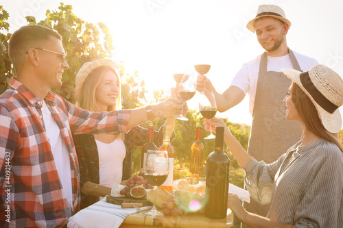 Friends holding glasses of wine and having fun in vineyard