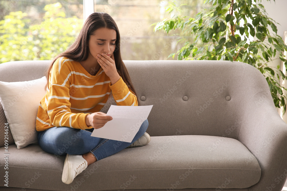 Fototapeta Worried woman reading letter on sofa at home