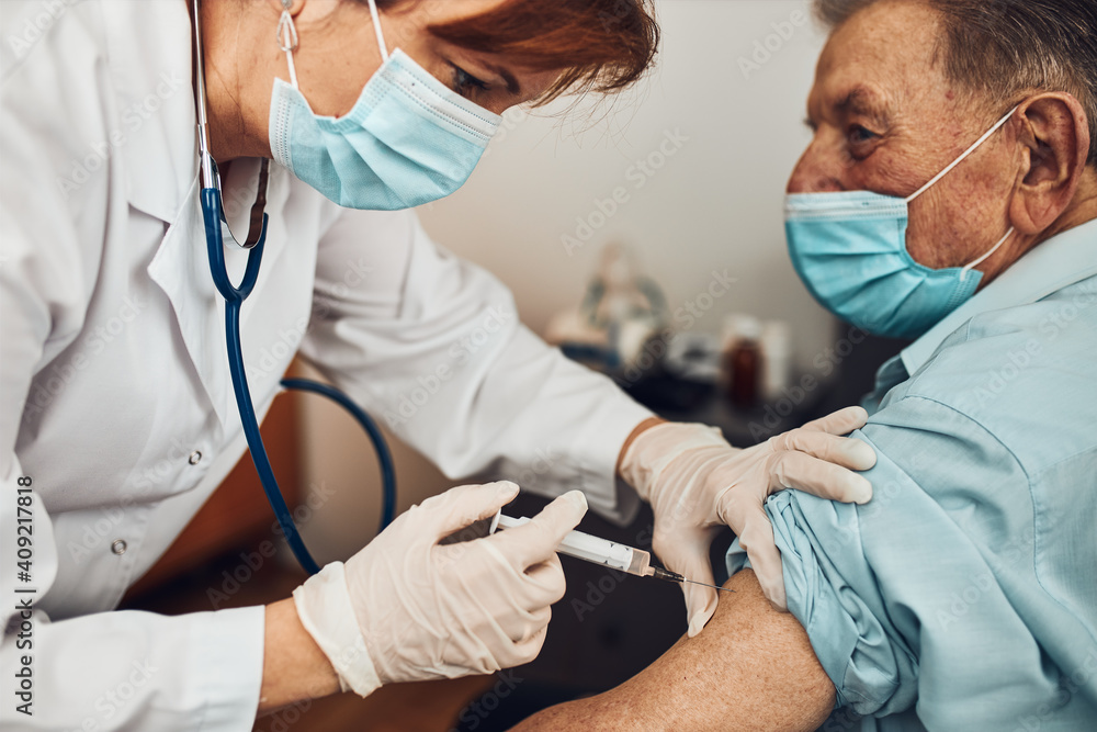 Fototapeta Doctor holding syringe with vaccine and making injection to senior patient with medical mask. Covid-19 or coronavirus vaccine. Protecting people against harmful diseases. Physician wearing white coat