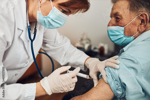 Fotografia Doctor holding syringe with vaccine and making injection to senior patient with medical mask