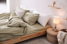 Comfortable Bed With Olive Green Linen In Modern Room Interior