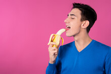 A Young Guy Is Eating A Banana. Diet And Fruits. Pink Background.