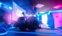 Professional Headphones With Microphone For Video Games And Cyber Sports Gaming Monitor In Neon Color Blur Background