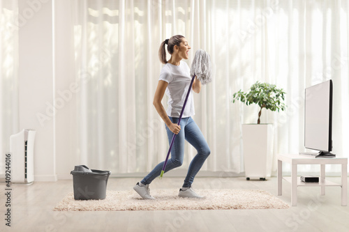 Fotografia Happy young woman dancing and singing with a cleaning mop in front of tv