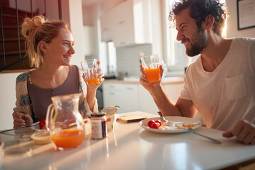 A happy young couple drinking a fresh orange juice after breakfast. Relationship, love, together, breakfast