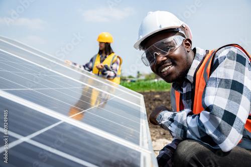 Valokuvatapetti Two workers technicians installing heavy solar photo voltaic panels to high steel platform in corn field