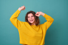 A Cheerful Model With Curly Hair Dances And Feels Joyful, Wearing A Yellow Sweater, Smiling Widely, Having Fun And Moving To The Rhythm Of Music Isolated On A Blue Background