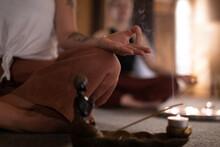 Anonymous Female Meditating Near Incense Smoke