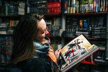 A Beautiful Woman In A Book Store Holds An Open Comic Book In The Ruffs (the Book Is Blurred).