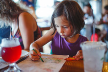 A Little Girl Sits At A Restaurant Table Coloring With Crayons