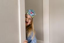 Smiling Cite Girl With Earth Day Headband Peeking Around Wall