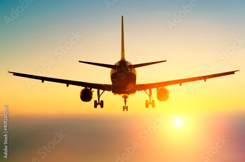 Obraz Passenger airplane landing on a runway in the evening fog during a bright red sunset. - fototapety do salonu