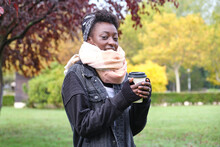 Beautiful Female African Woman Wearing A Scarf An Holding A Cup Of Coffee In A Park. Fall, Winter And Cold Concepts.