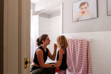 Mom And Daughter In Bathroom Taking Temperature With Thermometer