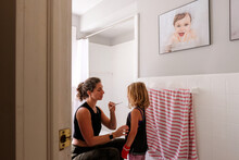 Mother And Daughter In Bathroom Reading Temperature On Thermometer