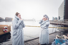 Two Friends Wearing Matching Robes After Cold Swim In Denmark