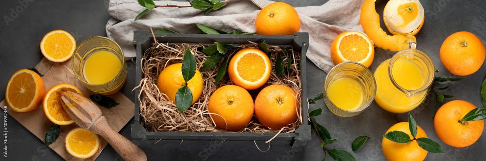 Fototapeta Oranges and juice in grey box on grey background