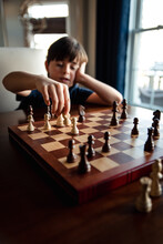 Young Pensive Boy Sitting Behind Chess Board Moving One Of The Pieces.