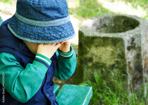 Fotografia a little boy in a blue vest and a Panama hat is crying in a park in the afternoon side view