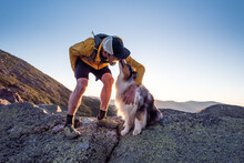 Dog Licking Owner's Face During Trail Running In Mountains