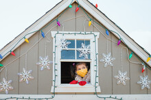 Young Girl In Face Mask Looking Out Window Christmas Decorations