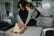 Father And Daughter Admiring Finished Gingerbread House