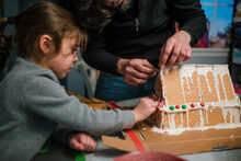 Dad And Daughter Building Gingerbread House In Kitchen