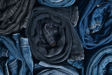 Stack Of Various Shades Of Blue Jeans On White Background Denim Jeans Texture. Denim Background Texture For Design. Canvas Denim Texture. Blue Denim That Can Be Used As Background.