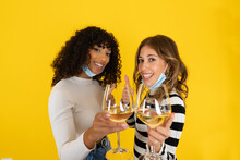 Two Young Women Isolated On Yellow Background Doing Thumb Up Sign Wearing Protection Mask Holding White Wine Glass And Smiling Looking At The Camera. Optimist Concept Of Celebrate End Of Pandemic
