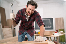 Hammering Fail. A Carpenter Wearing A Red Flannel Shirt, Jeans And Cloth Protective Gloves Screaming After Hitting A Finger With A Hammer.